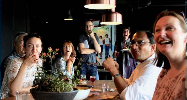 A group of people of different ages, genders and ethnicities sit at a table, looking up and smiling