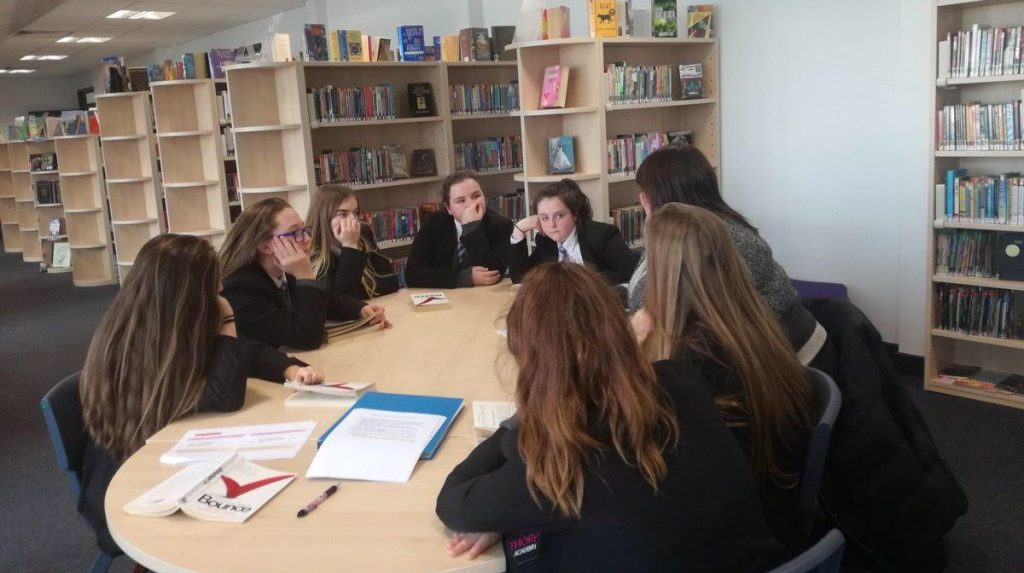 Group of school children sat around a table working with Melanie Cornish, founder of Bringing Words to Life