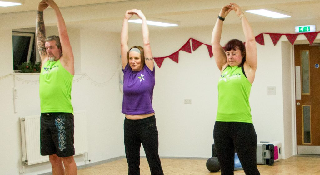 A group of people stretching as part of a Bodeeworx session