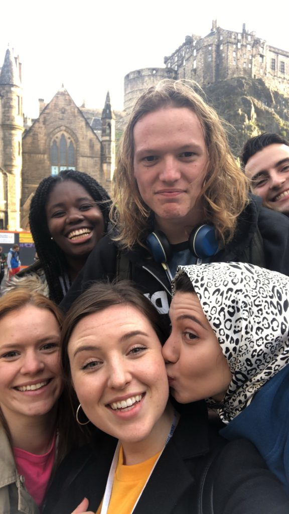 A selfie of 6 of the young programme participants smiling, with Edinburgh castle in the background