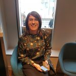Claire Prosho, founder of Claire's Transgender Talks, sitting down and smiling for the camera.
