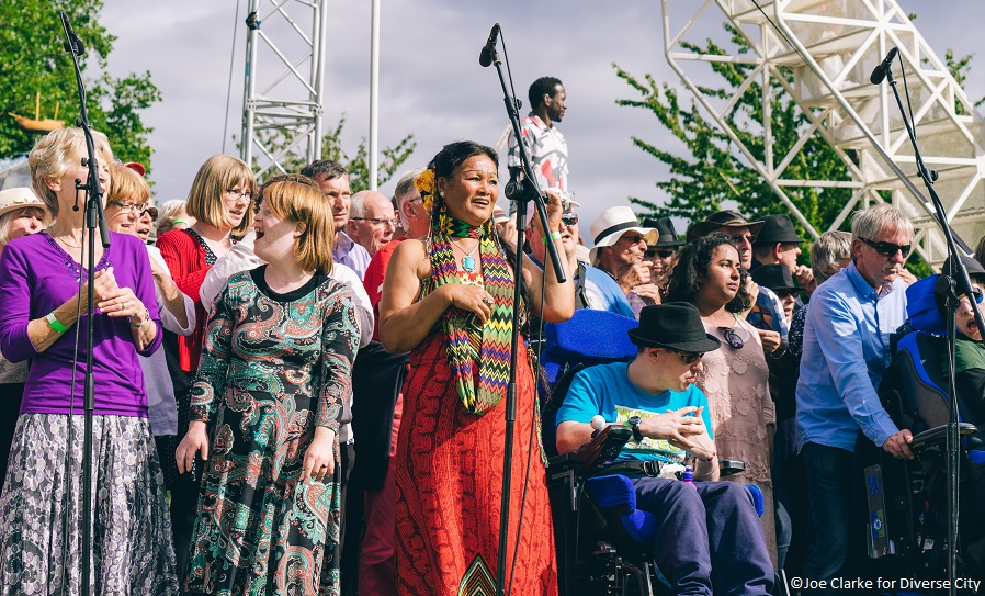 A group of people outdoors in front of microphones, taking part in an artistic event, including people of colour and a wheelchair-user