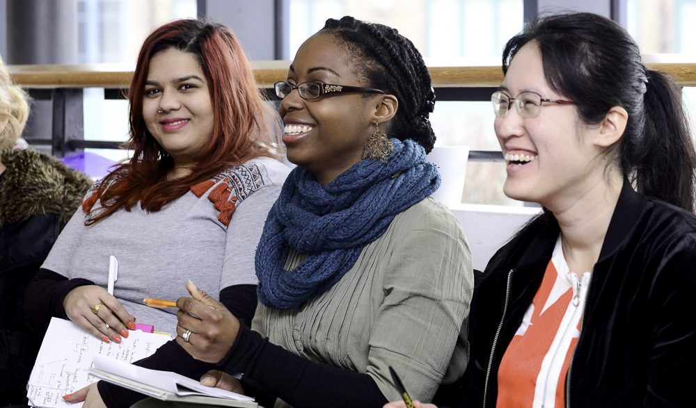 Three women of different ages and ethnicities sit smiling in a row with notebooks, learning
