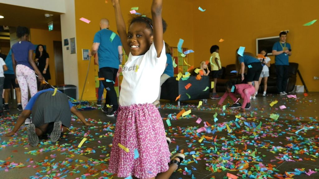 Young girl smiling with raised arms, confetti around her, and more children in the background - at Manchester Youth Zone