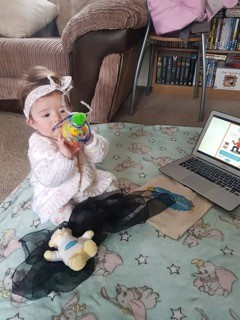 A toddler sits on the floor next to a laptop